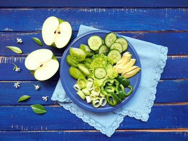 Verdure e frutta verdi - porro, cetriolo, insalata di lattuga, avocado, mela e pepe verde su superficie di legno blu