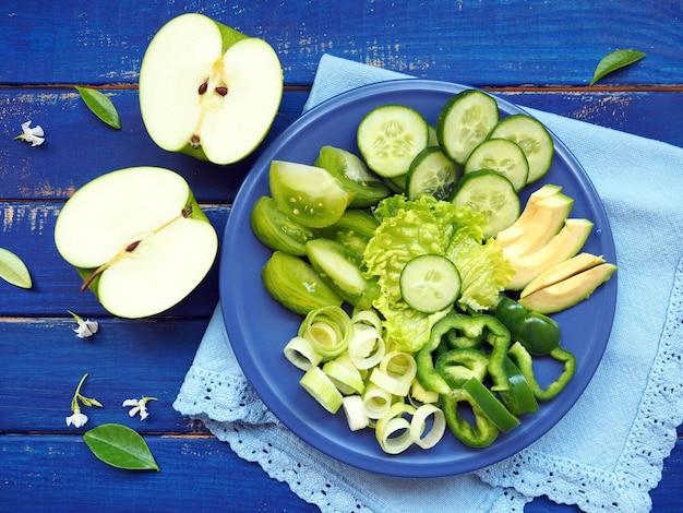 Verdure verdi e frutta - porro, cetriolo, insalata di lattuga, avocado, mela e pepe verde sulla tavola di legno blu