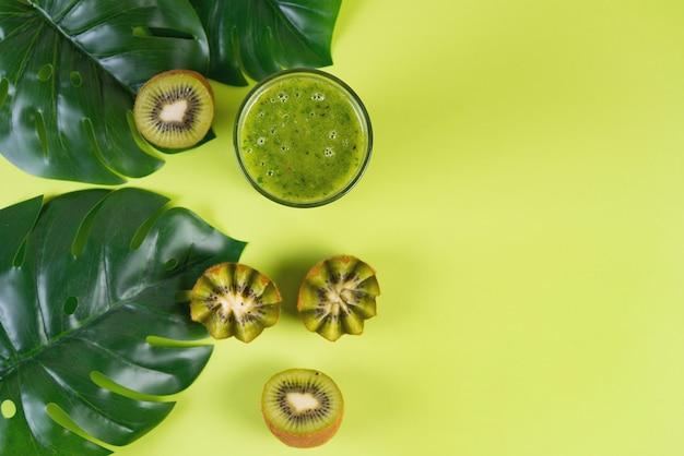Frullato vegetariano verde su un fondo verde con le metà del kiwi e le foglie tropicali, concetto dell'alimento pulito, vista superiore, copia di spazio