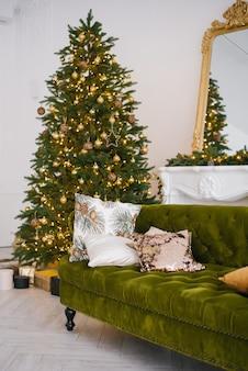 Il divano in velluto verde con cuscini nella luminosa mansarda ha un caminetto artificiale