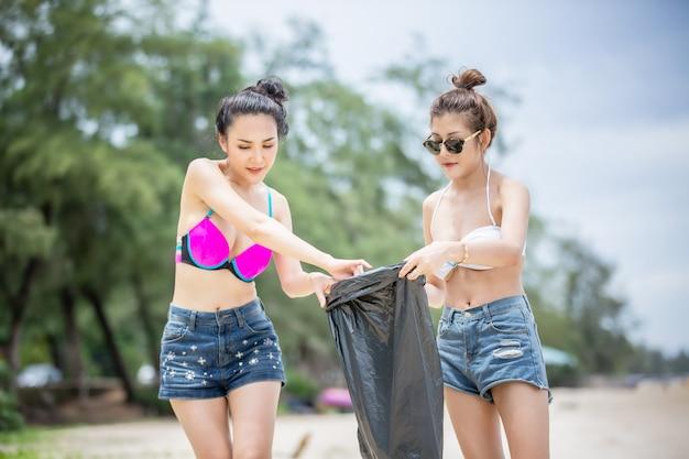 Volontariato verde. due volontari ottimisti che tengono in mano un sacco della spazzatura e aiutano a raccogliere la spazzatura al parco, raccolgono la spazzatura e la mettono in un sacco della spazzatura nero. concetto di protezione dell'ecologia.