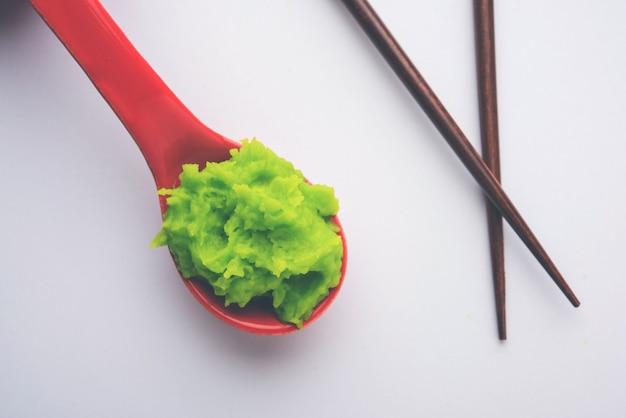 Salsa o pasta di wasabi verde in una ciotola, con le bacchette o un cucchiaio su uno sfondo colorato. messa a fuoco selettiva