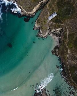 Drone di onde che si infrangono sulla spiaggia di acqua verde girato con cappella