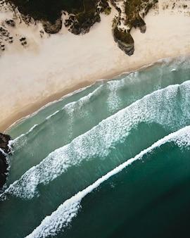 Acqua verde spiaggia deserta che si infrangono onde drone girato