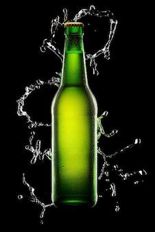 Bottiglia di birra bagnata verde sul nero con spruzzi d'acqua