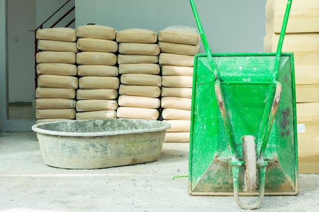Carriola verde e serbatoio di miscelazione del mortaio pila di cemento in sacchi marroni in un cantiere con sfondo grigio muro