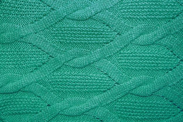 Fine di struttura del maglione di lana verde su. fondo in jersey lavorato a maglia con motivo a rilievo