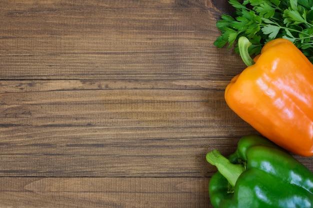 Peperoni verdi e gialli, con prezzemolo, su uno sfondo di tavolo in legno. vista dall'alto, bordo, cornice, piatto. copia spazio