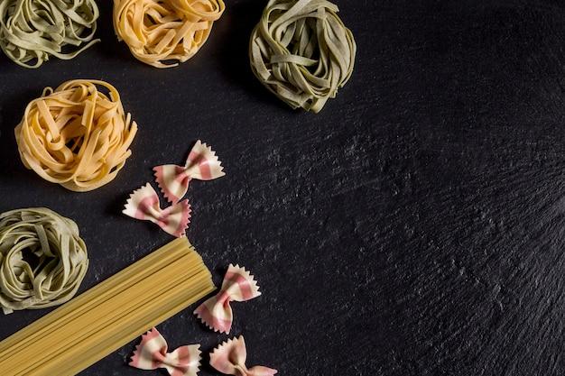 Tagliatelle verdi e gialle, spaghetti e farfalle di pasta su ardesia nera