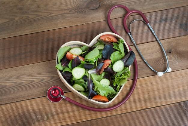 Insalata di verdi nel piatto e nello stetoscopio di legno a forma di cuore.