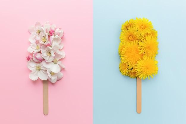 Il collage di concetto di biglietto di auguri piatto giaceva su sfondo rosa e blu con lecca lecca di gelato di fiori di mela e dente di leone su un bastoncino
