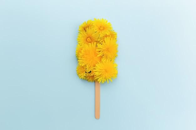 Il concetto di biglietto di auguri piatto giaceva su sfondo blu con lecca-lecca di gelato di fiori di dente di leone su un bastone. foto di alta qualità