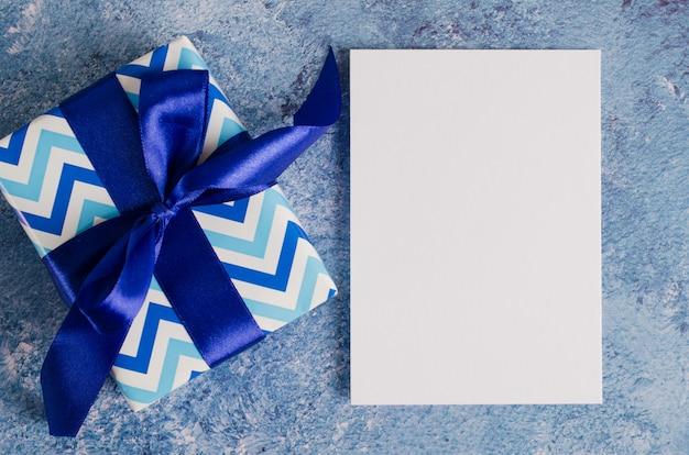 Biglietto di auguri per la festa del papà o il compleanno. contenitore di regalo con libro bianco in bianco su fondo blu.