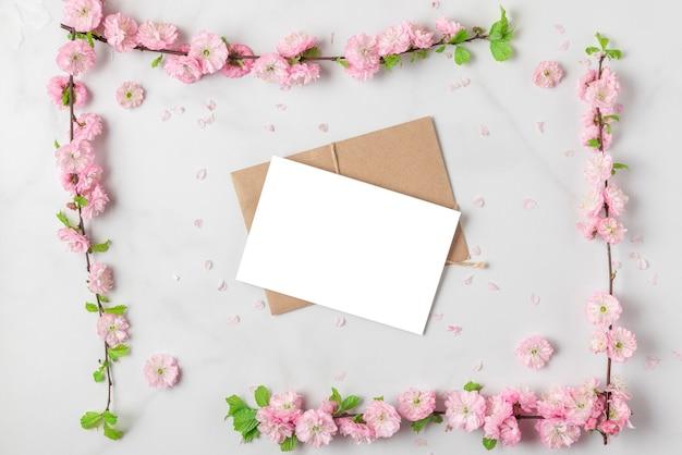 Biglietto di auguri in cornice fatta di rami di fiori di ciliegio rosa primavera su sfondo bianco marmo. lay piatto. vista dall'alto. layout per vacanze o matrimoni con copia spazio