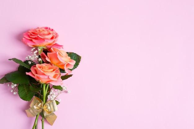 Biglietto di auguri dal bouquet naturale di rose appena raccolte fiori su uno sfondo rosa pastello.