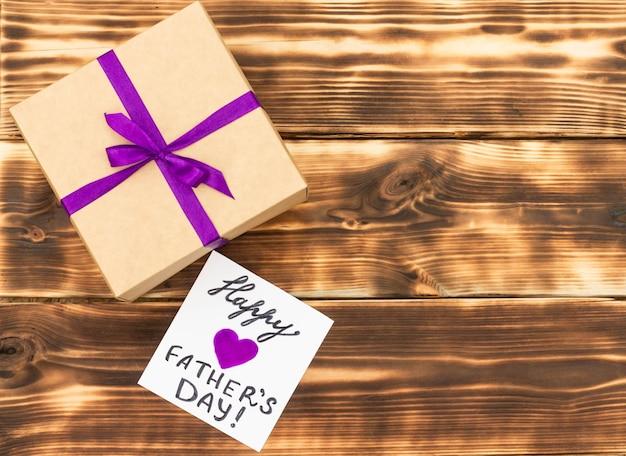 Biglietto di auguri per la festa del papà felice con una confezione regalo su un tavolo in legno rustico