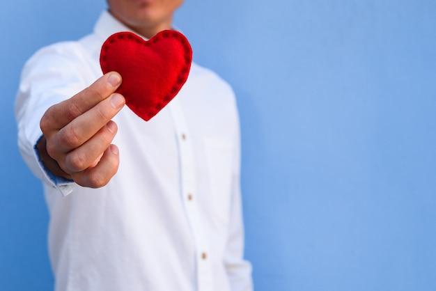 Biglietto di auguri per buon san valentino. il ragazzo sullo sfondo del muro blu dà un cuore rosso
