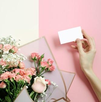 Mockup di biglietto di auguri in un bouquet di rose rosa, foto vista dall'alto