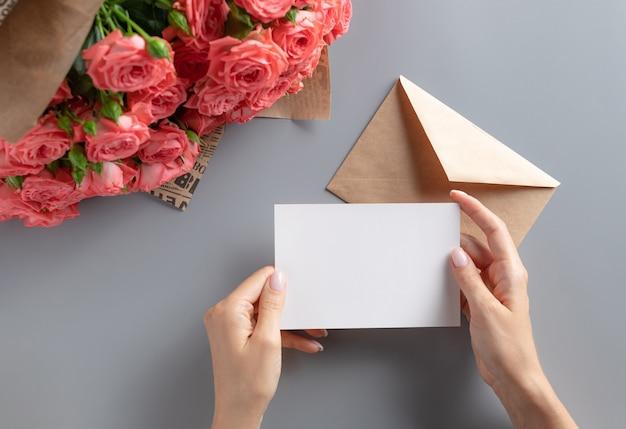 Scena del modello del biglietto di auguri con la mano della donna che tiene la carta di carta bianca
