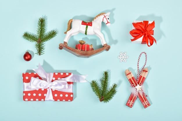 Biglietto di auguri per capodanno e natale. un banner festivo con regali e giocattoli di natale su uno sfondo azzurro. layout piatto, vista dall'alto. copia spazio.