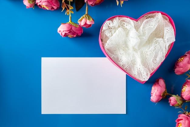 Biglietto di auguri e confezione regalo aperta su sfondo blu. biglietto di auguri vuoto e confezione regalo a forma di cuore rosa aperta su sfondo blu. posto per testo, design per san valentino.