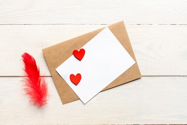 Modello di biglietto di auguri con busta di carta artigianale e cuori e piume rosso brillante