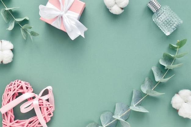 Un biglietto di auguri per san valentino. cornice per testo fatta di eucalipto, regalo e cuore su sfondo verde. lay piatto, vista dall'alto, copia spazio.