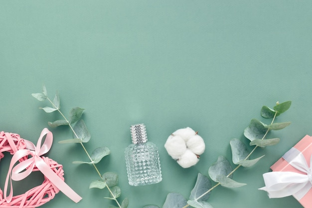 Un biglietto di auguri per san valentino. cornice per testo fatta di eucalipto, regalo e cuore su sfondo verde. lay piatto, vista dall'alto, copia spazio. Foto Premium