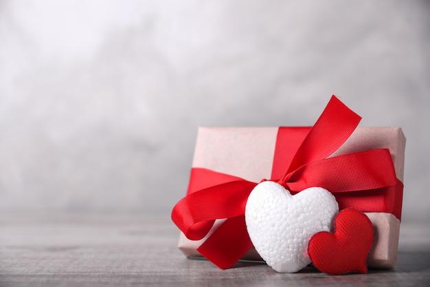 Cartolina d'auguri di san valentino con cuori su fondo in legno e regalo. con i saluti dello spazio