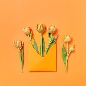 Biglietto di auguri con busta artigianale di tulipani gialli su sfondo arancione. lettera d'amore come regalo. vista dall'alto.