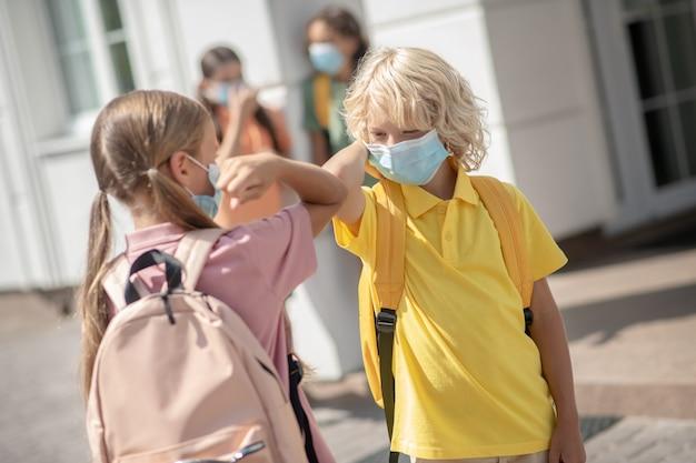 Saluto. i bambini in maschere protettive nel cortile della scuola si salutano