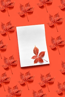 Saluto cartolina d'autunno con carta bianca vuota e foglie di vite rossa biologica