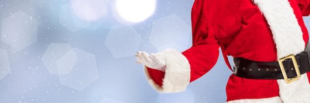 Volantino di auguri per annuncio. concetto di natale, capodanno 2021, umore invernale, vacanze. copyspace, cartolina. babbo natale in costume tradizionale che mostra, puntando su sfondo blu bokeh. orizzontale