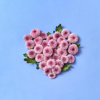 Cartolina d'auguri con cuore di fiori di crisantemo resistente su uno sfondo pastello, luogo per il testo. lay piatto.