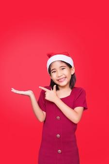 Saluto la ragazza di babbo natale indica di consigliare il prodotto a portata di mano e copiare lo spazio sulla testa superiore sul muro rosso isolato