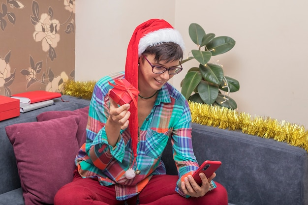 Auguri di natale online: la donna a casa con un cappello da babbo natale con doni parla online tramite smartphone