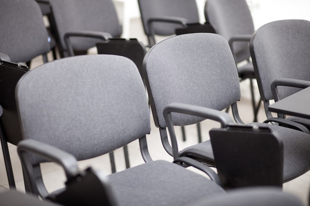 Poltrone grigie in una sala conferenze vuota.