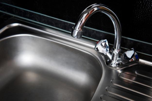 Lavandino pulito grigio e rubinetto per acqua calda sanitaria in metallo. cucina argento lavello decorazione moderna casa in acciaio inox su uno sfondo nero scuro.