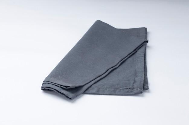 Tovagliolo di colore grigio disposto su sfondo bianco strutturato, fuoco selettivo isolato.