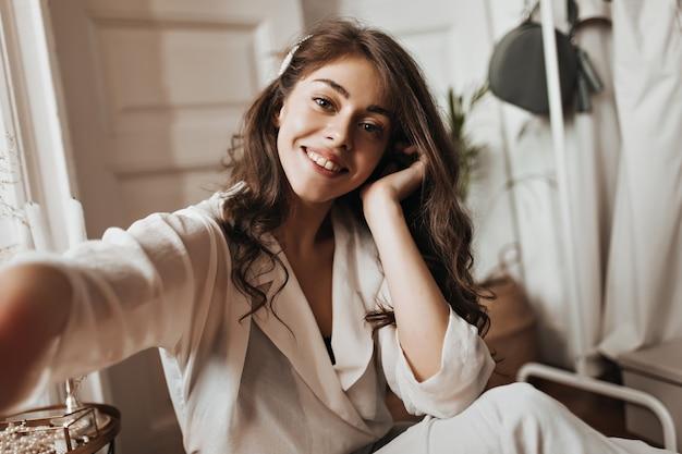 Donna dagli occhi grigi in camicetta bianca che prende selfie
