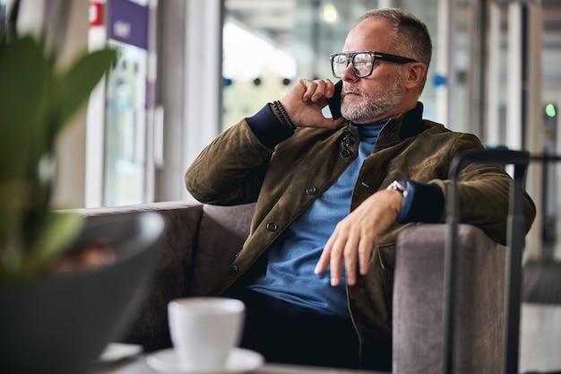 Uomo caucasico dai capelli grigi che fa una telefonata