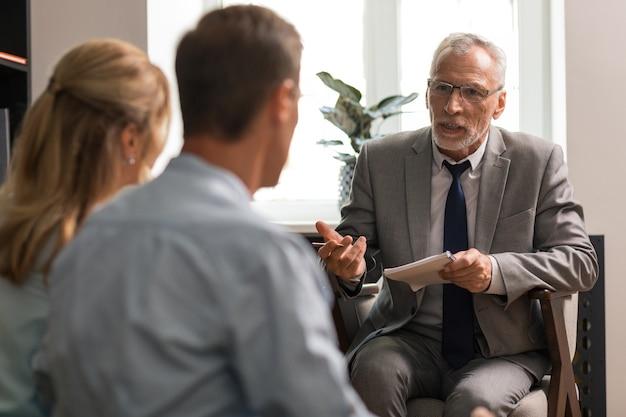 Psicologo senior caucasico dai capelli grigi che parla con una coppia seduta davanti a lui durante la sessione di terapia
