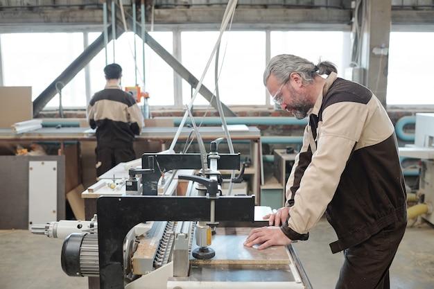 Operaio maturo dai capelli grigi della scheda di fissaggio in fabbrica sul banco di lavoro mentre lo elaborerà sulla macchina industriale nell'ambiente di lavoro