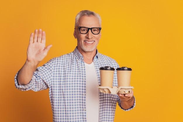 L'uomo anziano dai capelli grigi tiene una bevanda calda al caffè in una tazza da asporto
