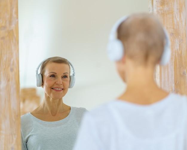 Donna anziana dai capelli grigi con le cuffie che si ammira allo specchio