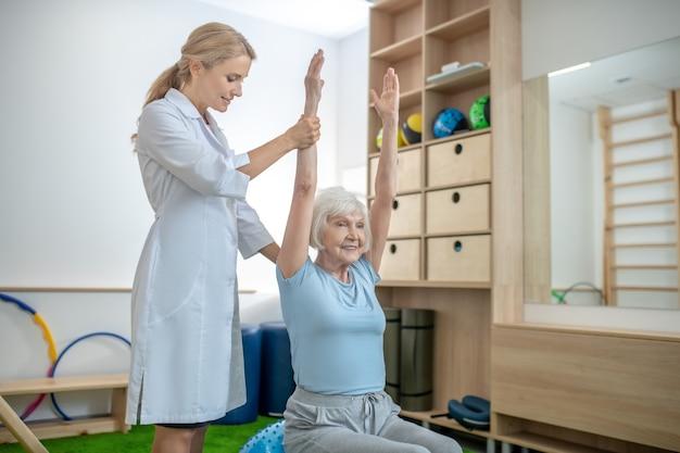 Donna dai capelli grigi che si esercita in un centro di riabilitazione con istruttore