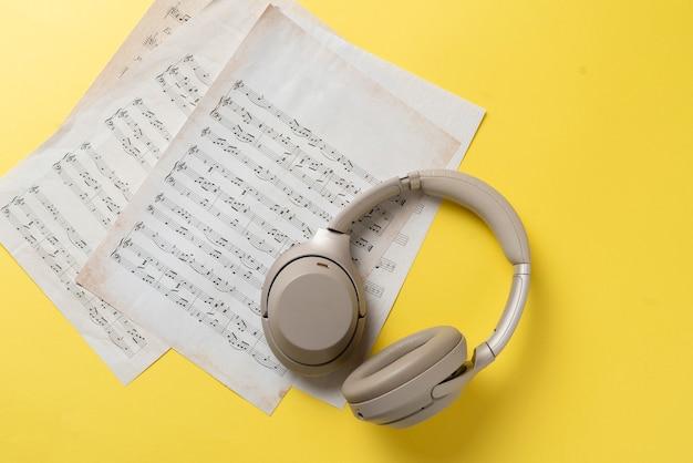 Una cuffia grigia sul foglio di carta delle note musicali