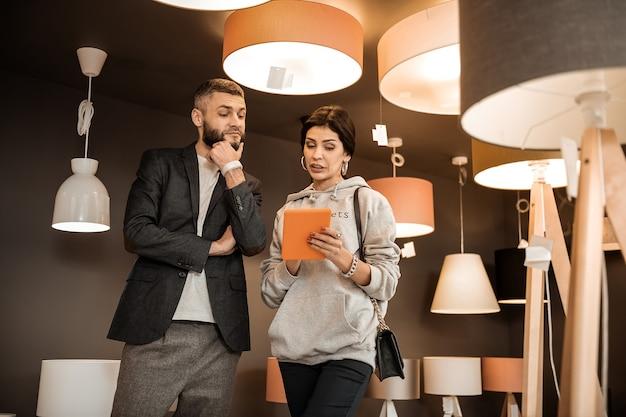 In felpa con cappuccio grigia. donna seria risoluta che indica sul tablet mentre mostra i mobili necessari al consulente interessato nelle vicinanze