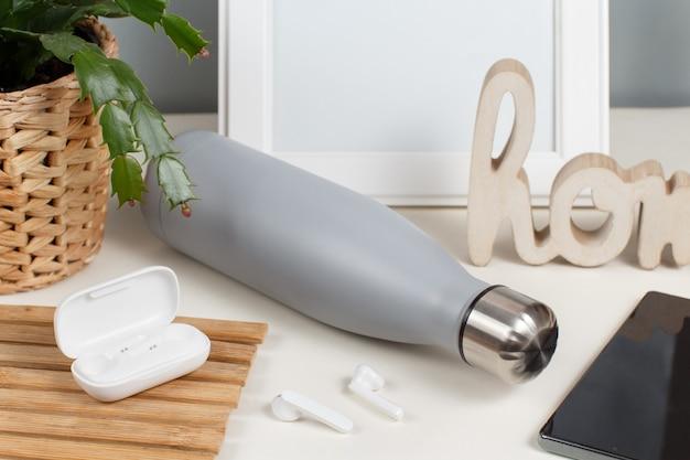 Bottiglia isolata grigia sulla scrivania bianca circondata da gadget moderni