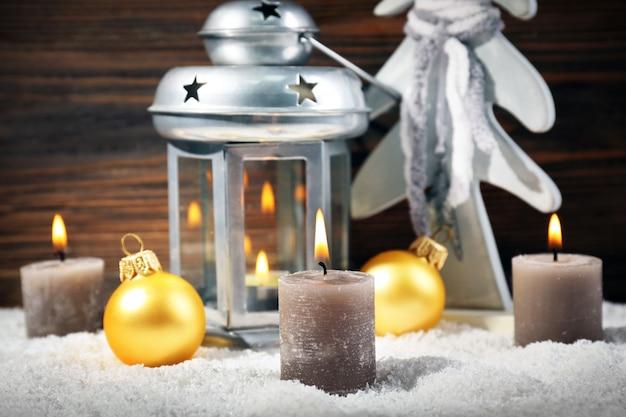 Lampada grigia, abete, candele e palline in una neve su sfondo di legno, primo piano